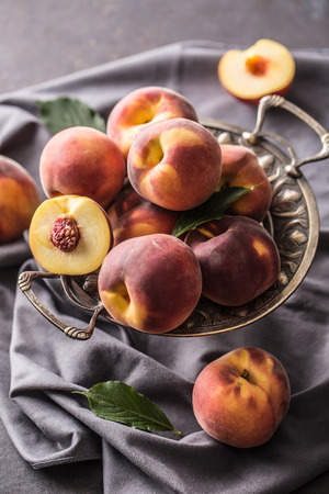 A group a ripe peaches in rustic bowl.