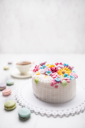 Cake from marzipan flowers macaroons and a cup of black coffee. Archivio Fotografico