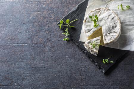 Cheese camambert from oregano herbs on slate board.