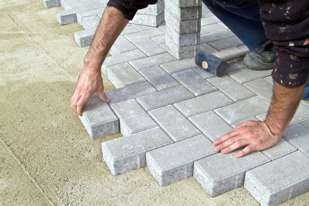 Bricklayer prfessional at work on the sidewalk saves tiles. Imagens