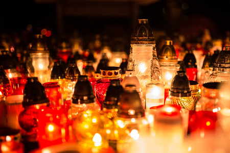 Many burning candles in the cemetery at night on the occasion souls of the deceased. 免版税图像