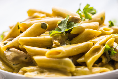 Pasta pene with chicken pieces mushrooms parmesan cheese sauce and herb decoration. Pene con pollo - Italian or medierranean cuisine.