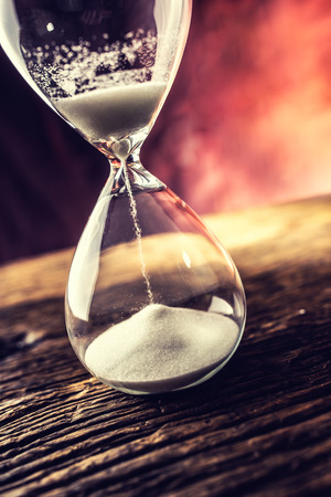 Modern hourglass in running time on wooden table.