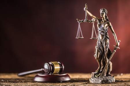 Lady Justicia holding sword and scale bronze figurine with judge hammer on wooden table. Stockfoto