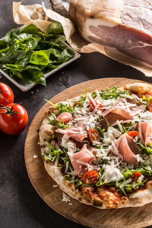 Italian pizza with prosciutto arugula tomatoes and parmesan on wooden round board.
