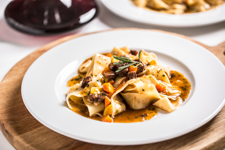 Idalian pasta pappardelle with beef ragu on white plate and red wine.