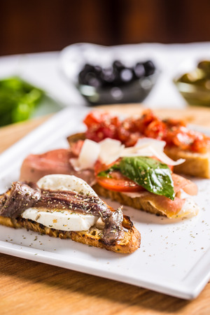 Tasty italian appetizer bruschettes with tomatoes anchovies prosciutto and mozarella.