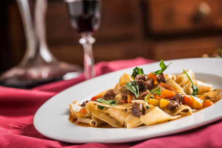 Idalian pasta pappardelle with beef ragout on white plate and red wine.