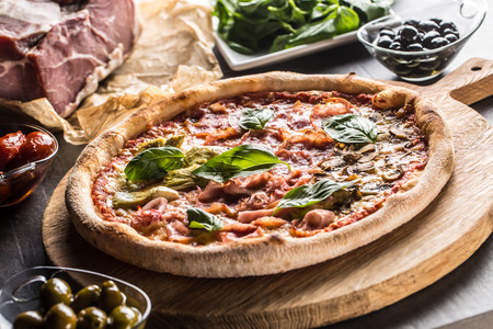 Pizza Quatro Stagioni four seasons traditional italian meal from artichokes mushrooms tomatoes ham prosciutto parmesan cheese and basil.