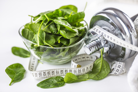 Spinach dumbbells and measure tape isolated on white background. Stock Photo