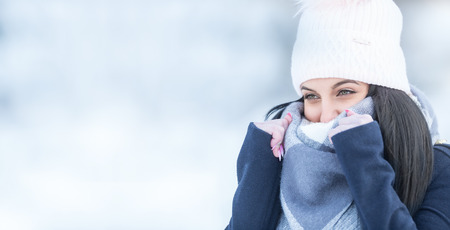Winter portrait of beautiful girl with woolen scarf.