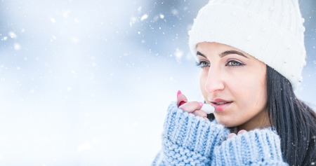 Attractive young woman l protecting lips with lip balm in snowy and frozen weather.