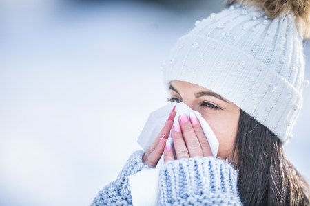 Attractive young woman blowing her nose with a tissue in winter.