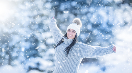 Winter portrait of happy attractive young woman in warm clothing