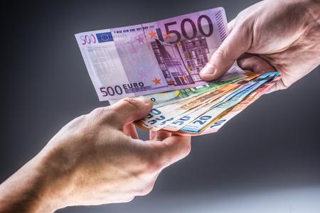 Mannelijke handen met eurobankbiljetten en de andere hand om steekpenningen te ontvangen.
