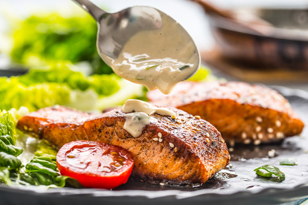 Delicious grilled roasted salmon fillets or steaks with mushroom sauce sesame tomatoes and lettuce salad. Stock Photo
