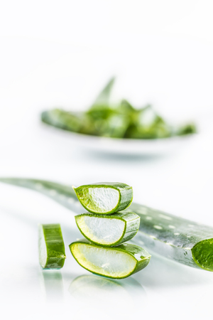 Slices of aloe vera with gel on white background.