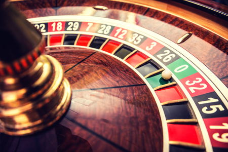 Roulette wheel in casino with ball on green position zero.