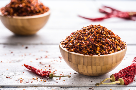 Dried and crushed chili peppers in wooden bowles. Stock Photo