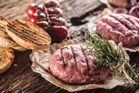 Raw burgers on wooden table with onion tomatoes herbs and spices.