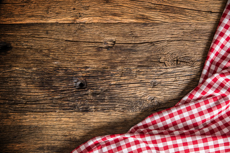 Red checkered kitchen tablecloth on rustic wooden table. Фото со стока
