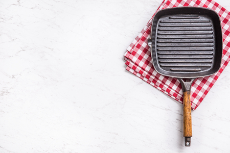 Empty grill pan on marble table with red tablecloth - top of view.