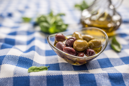 Green and red olives in bowl with olive oil and carafe in the background.