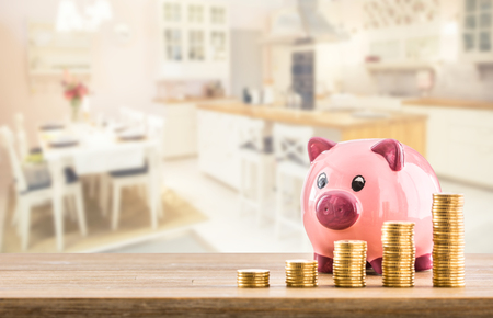 Pink piggy bank coins and modern kitchen interior in the background. Bank construction or insurance concept.