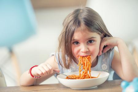 Niña linda niño comiendo espaguetis a la boloñesa en casa.