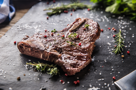 Beef T-Bone steak with salt pepper and rosemary on slate plate. Stock Photo