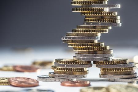 Monete in euro impilate l'una sull'altra in posizioni diverse. Soldi e valuta europei del primo piano.