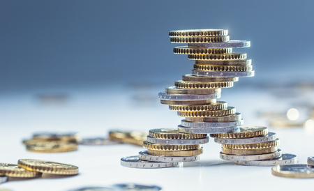 Monedas de euro apiladas unas sobre otras en diferentes posiciones. Moneda y dinero europeos de primer plano. Foto de archivo