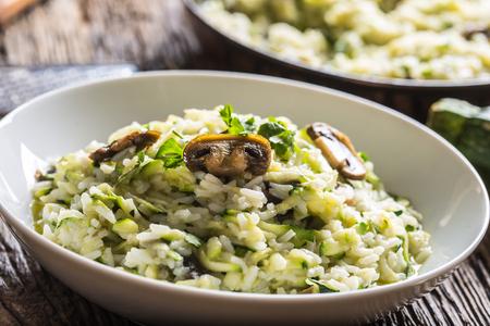 Italian risotto zucchini mushrooms and parmesan in white plate.