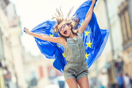Cute happy young girl with the flag of the European Union.