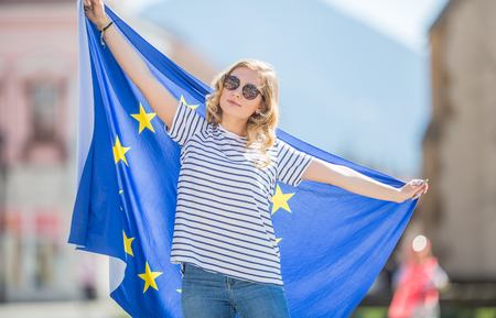 Attractive happy young girl with the flag of the European Union.