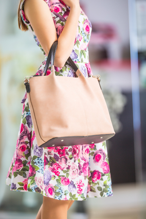 Close-up woman sexy legs summer outfit handbag and shoes. Stylish casual woman in shopping mall.