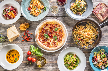 Top of view full table of italian meals on plates and pan. Pizza pasta risotto soup and fish vegetable salad. Imagens