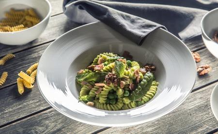 Fusilli pasta with green peas ham and walnuts. Italian or Mediterranean cuisine.