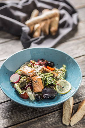 Fresh vegetable salad with roasted salmon olive oil and baguette.