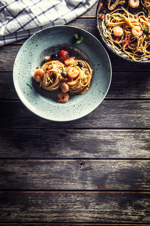 Pasta spaghetti on plate and pan with shrimp tomato sauce tomatoes and herbs. Italian or Mediterranean cuisine.