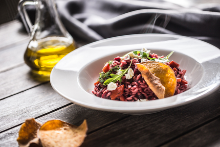 Beetroot risotto with feta cheese potato chips arugula and olive oil.