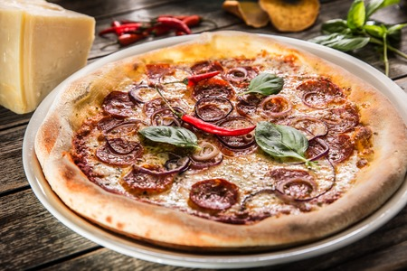 Pizza salami diavola with red onion basil and chili pepper.