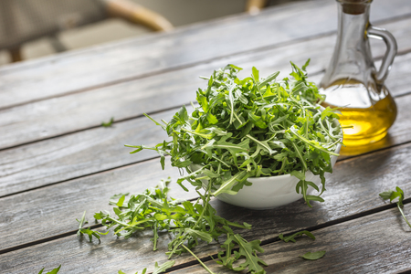 Fresh arugula salad with olive oil  in white dish on wooden table.