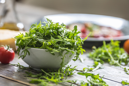Fresh arugula salad in white dish on wooden table.