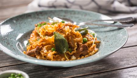 Italian pasta mafalde mushrooms peas and tomato sauce.