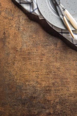 Top of view knife fork plate at napkin on empty rust background. Stock Photo
