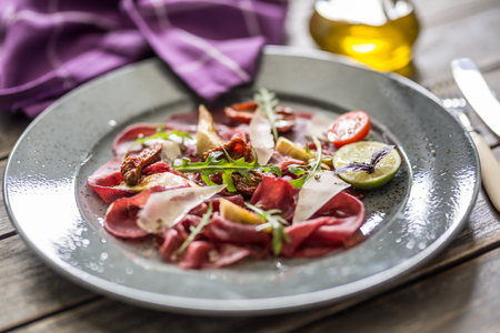 Beef carpaccio on plate with dried tomatoes artichokes arugula and parmesan cheese. Stock Photo
