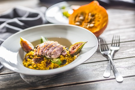 Pumpkin risotto roasted duck breast figs zucchini and min leaves. italian or mediterranean cuisine.
