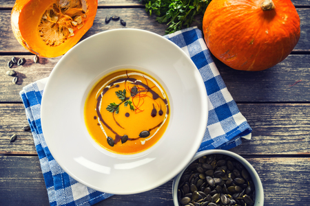 Pumpkin cream soup with seeds and parsley on kitchen table.
