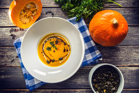 Pumpkin cream soup with seeds and parsley on kitchen table - Top of view.